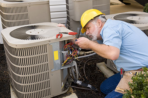 HVAC repair technician diagnosing systems for local business