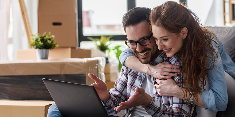 Young couple homeowners on couch face laptop and read AC energy efficiency tips.